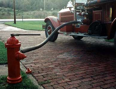 Photo of early Darling hydrant connected to 1929 American LaFrance pumper